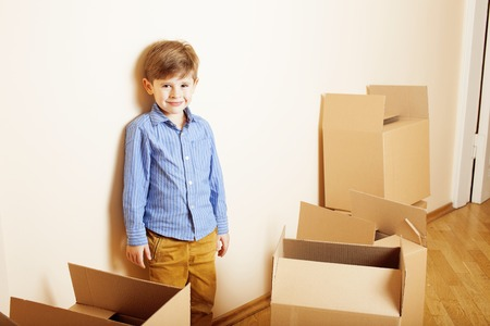 house moving: little cute boy in empty room, remoove to new house. home alone emong boxes close up kid Stock Photo