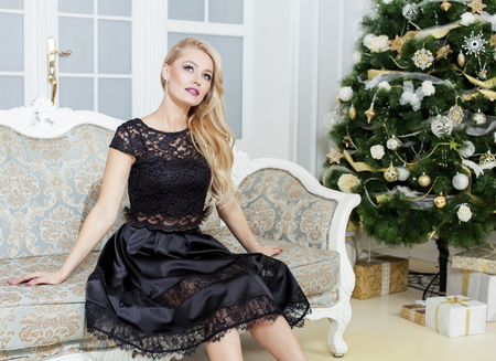 new age: mature middle age woman in rich interior decorated for Christmas. Beautiful blond female smiling at home. Waiting for guests night, new year eve