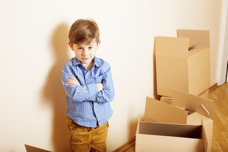 cool guy: little cute boy in empty room, remoove to new house. home alone emong boxes close up kid Stock Photo