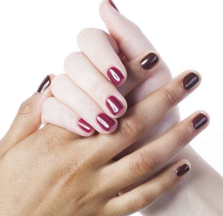 manicured hands: two different nathion manicured hands on white isolated, african with caucasian close up, concept friendship of nations
