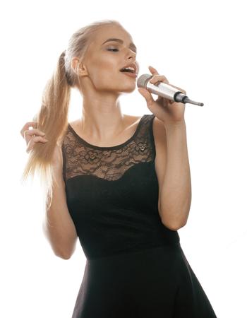 rubia: joven mujer que canta bastante rubia en el micrófono aislado cerca de vestido negro, niña karaoke pequeña estrella Foto de archivo