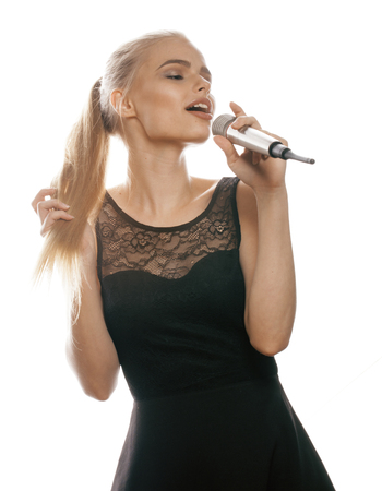 blonde woman: young pretty blond woman singing in microphone isolated close up black dress, karaoke girl little star