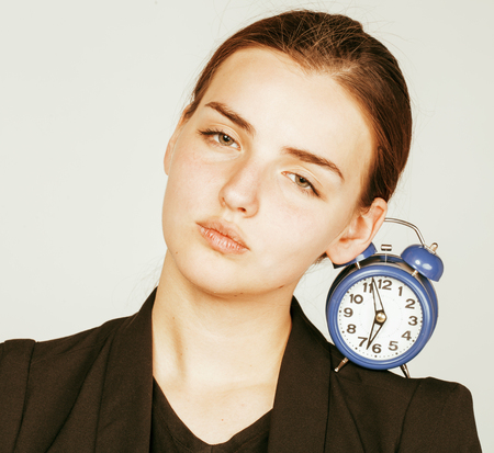 business costume: young beauty woman in business style costume waking up for work early morning on white background with clock dreanking coffee