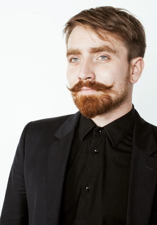 pelo rojo: joven hombre de pelo rojo con barba y bigote en traje negro sobre fondo blanco de cerca