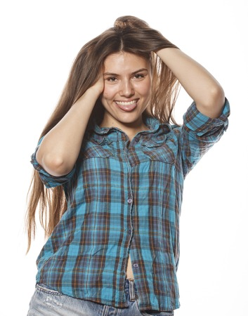 messing: young pretty woman posing on white background isolated emotional hipster student thinking smiling, messing hair