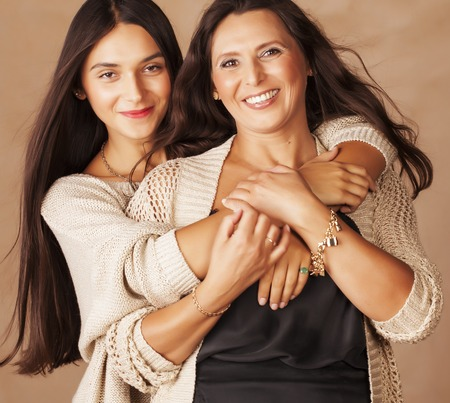 two girls hugging: cute pretty teen daughter with mature mother hugging, fashion style brunette makeup close up tann mulattos together, warm colors Stock Photo