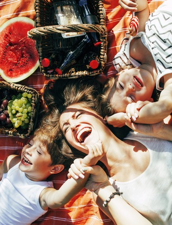 cute happy family on picnic laying on green grass mother and kids, warm summer vacations close up, brother and sisterhood Standard-Bild