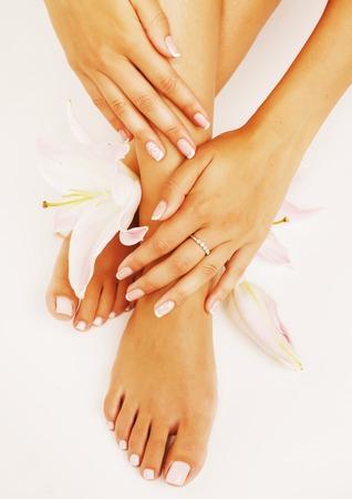 pedicura: mujer manicure pedicure con la flor del lirio de cerca aisladas en blanco de forma perfecta las manos