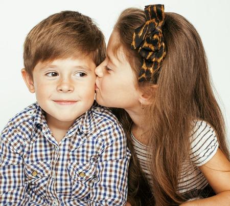 Weinig leuke jongen meisje knuffelen spelen op een witte achtergrond, gelukkige familie close-up geïsoleerd. broer en zus glimlachen knuffelen