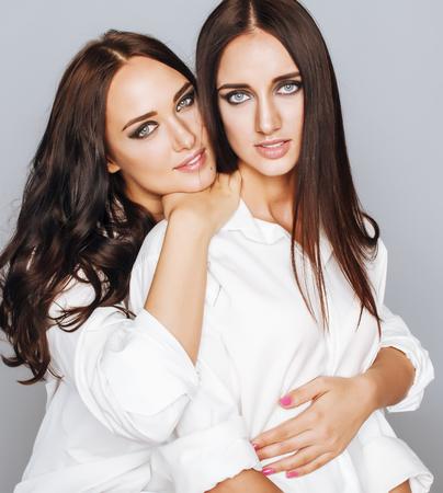 mejores amigas: dos hermanas gemelas posando, haciendo fotos selfie, vestido misma camisa blanca, diversos amigos peinado close up