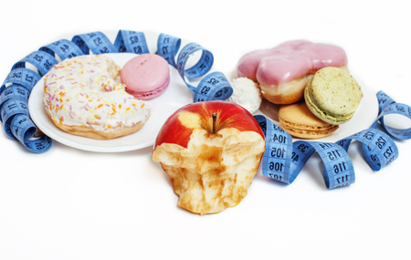 eating questions: new diet concept, question sign in shape of measurment tape between red apple and donut plus candy isolated on white