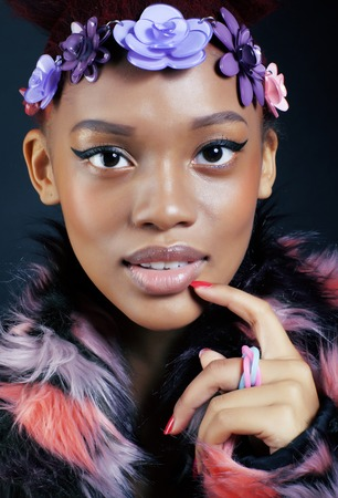 spotted fur: young pretty african american woman in spotted fur coat and flowers jewelry on head smiling sweet etnic make up bright closeup