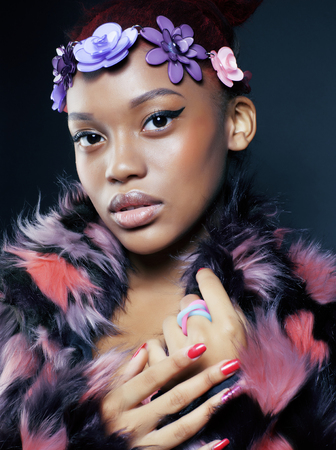 etnic: young pretty african american woman in spotted fur coat and flowers jewelry on head smiling sweet etnic make up bright closeup