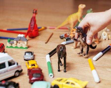 free education: children playing toys on floor at home, little hand in mess, free education concept