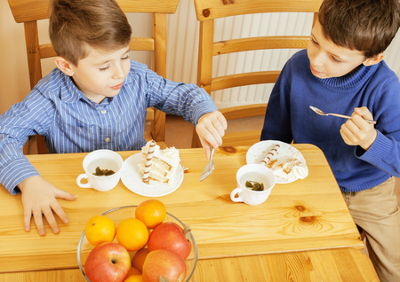 children eating: little cute boys eating dessert on wooden kitchen. home interior. smiling adorable indoor Stock Photo