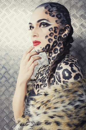 bodyart: young sexy woman with leopard make up all over body, cat bodyart closeup, professional faceprint