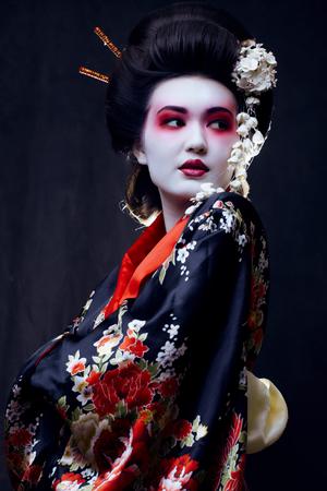 geisha kimono: young pretty real geisha in kimono with sakura and decoration