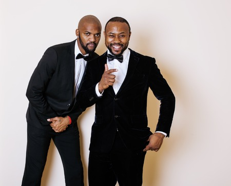 dinky: two afro-american businessmen in black suits emotional posing, gesturing, smiling. wearing bow-ties, party event menegers concept Stock Photo