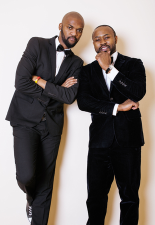two afro-american businessmen in black suits emotional posing, gesturing, smiling. wearing bow-ties, party event menegers concept Stock Photo