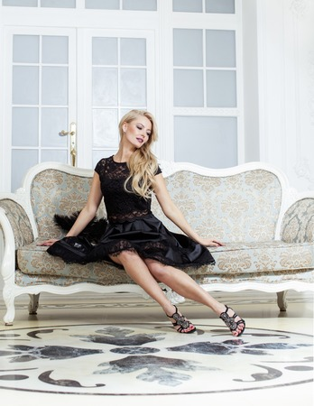 elegant dress: stylish elegant blonde woman in beauty rich interior, wearing black dress smiling. mature fashion concept