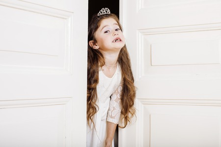 welldressed: little cute girl at home, opening door well-dressed in white dress, adorable milk fairy. front teeth gone