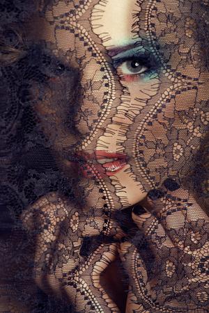 femme bouche ouverte: portrait de la beauté jeune femme à travers la dentelle noire close up mistery fée maquillage