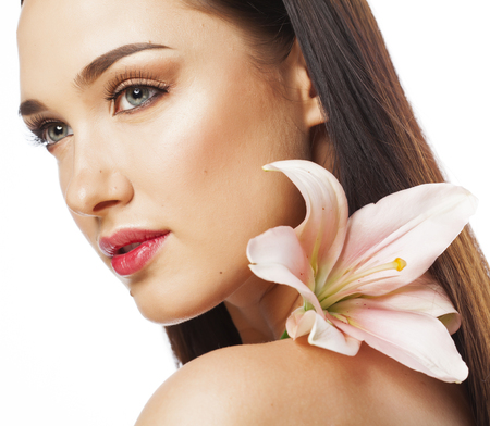 cuerpo perfecto femenino: atractivo joven de cerca con las manos en la cara aislada flor del lirio de spa morena desnuda maquillaje de primavera Foto de archivo