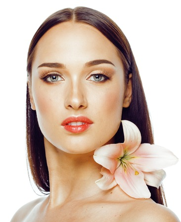 beautiful body: young attractive lady close up with hands on face isolated flower lily brunette spa nude spring makeup Stock Photo