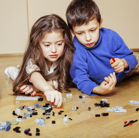 funny cute children playing lego at home, boys and girl smiling, first education role close up Standard-Bild