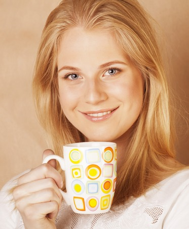 habbit: young cute blond caucasian girl drinking coffee close up on warm brown background