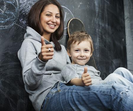 教室、国際的な多様な家族に彼女の兄と一緒に座っている若い流行に敏感な 10 代の少女
