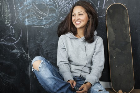 young cute teenage girl in classroom at blackboard seating on table smiling close up Standard-Bild