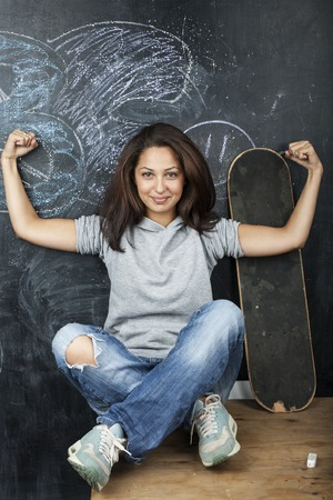 normal school: young cute teenage girl in classroom at blackboard seating on table smiling close up Stock Photo