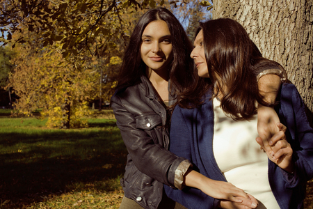 mature real mother with daughter outside autumn fall in park smiling