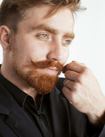 boy long hair: young red hair man with beard and mustache in black suit on white background close up