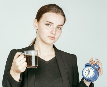 business costume: young beauty woman in business style costume waking up for work early morning on white background with clock dreanking coffee close up Stock Photo