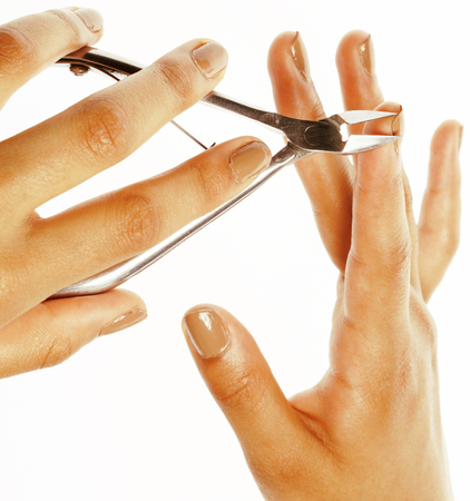 depraved: woman hands making no qualified manicure, pedicure to herself isolated with tools close up