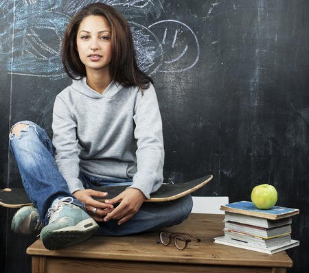 one teenager: young cute teenage girl in classroom at blackboard seating on table smiling, modern hipster concept