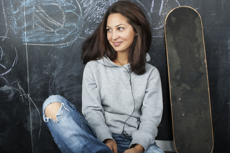 teens: young cute teenage girl in classroom at blackboard seating on table smiling, modern hipster concept