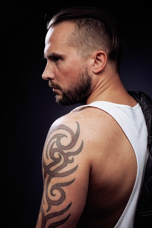 muscular arm: A man with tattooes on his arms. Silhouette of muscular body. caucasian brutal hipster guy with modern haircut, looking like criminal close up