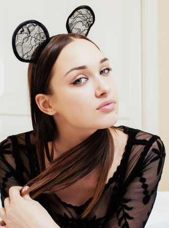 young pretty brunette woman wearing sexy lace mouse ears, laying waiting dreaming in bed alone