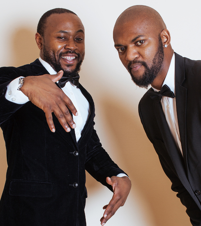 dinky: two afro-american businessmen in black suits emotional posing, gesturing, smiling. wearing bow-ties entertainment