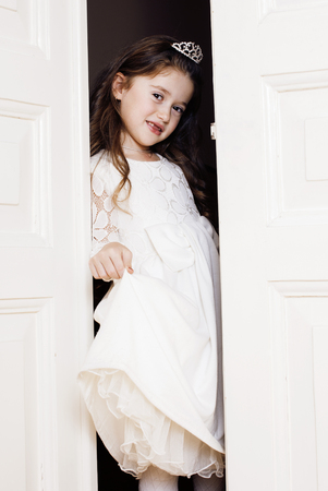 welldressed: little cute girl at home, opening door well-dressed in white dress, adorable milk fairy teeth close up