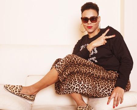 よく服を着てかなりスタイリッシュなアフリカ系アメリカ人のビッグママ女性。盗品は服にヒョウ柄を自宅でリラックスしてください。ファッショ 写真素材
