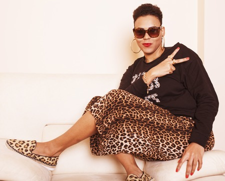 donne obese: pretty stylish african american big mama woman well dressed. swag relax at home, leopard print on clothers. fashion look