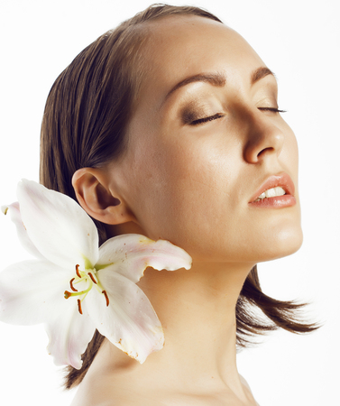 mature people: young attractive lady close up with hands on face isolated flower lily,spa woman