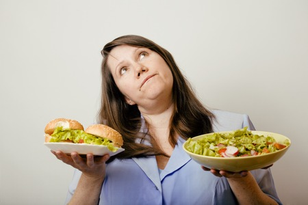 unhealth: fat white real woman having choice between hamburger and salad close up, unhealth fast food