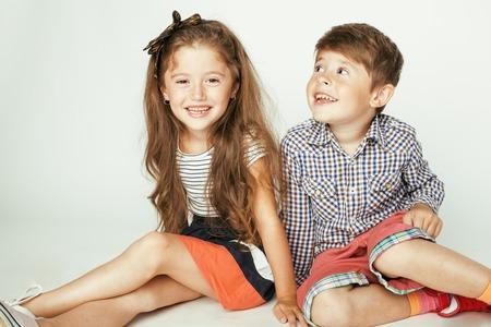 gemelos niÑo y niÑa: pequeño muchacho lindo y abrazos niña jugando en el fondo blanco, familia feliz sonriendo, hermano hermandad