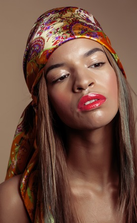 swag: beauty young afro american woman in shawl on head smiling close up swag concept