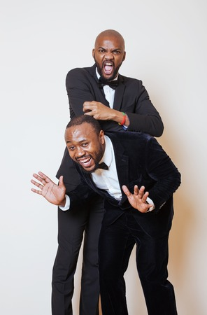 dinky: two afro-american businessmen in black suits emotional posing, gesturing, smiling. wearing bow-ties close up